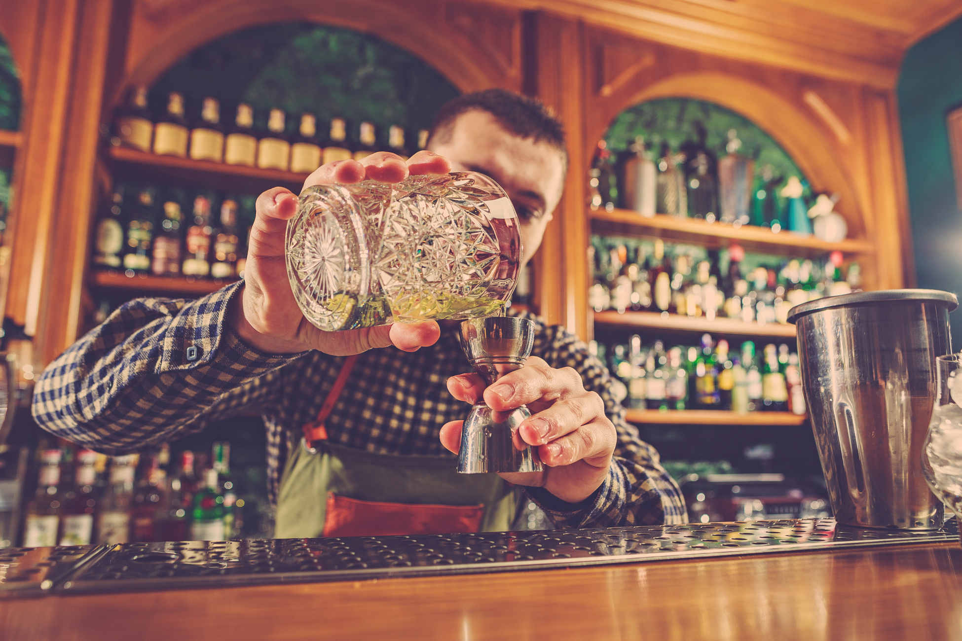The barman making an alcoholic cocktail at the bar counter on the bar background